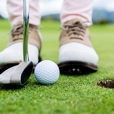 Closeup of a golfer's shoes, putter and golf ball on the greens