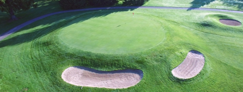 Aerial view of a golf hole with a red flag